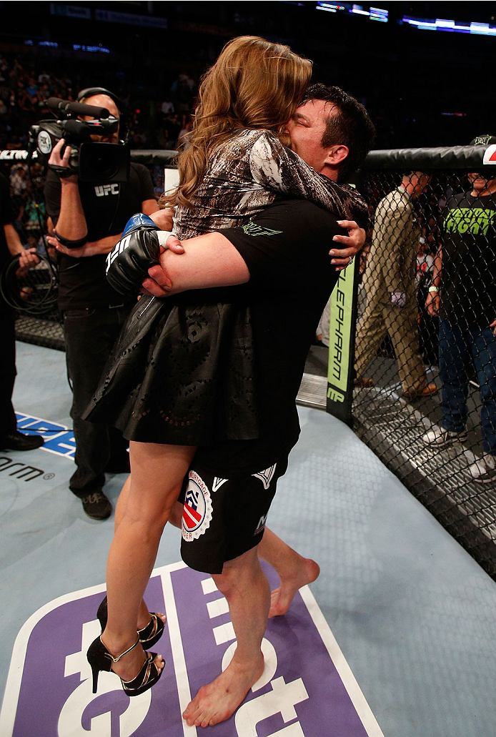 """BOSTON, MA - AUGUST 17:  (R-L) Chael Sonnen celebrates with his wife Brittany after his submission victory over Mauricio """"Shogun"""" Rua in their UFC light heavyweight bout at TD Garden on August 17, 2013 in Boston, Massachusetts. (Photo by Josh Hedges/Zuffa"""