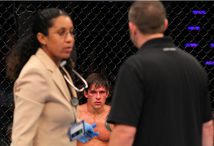 INDIANAPOLIS, IN - AUGUST 28:  Roger Bowling looks on as the doctor and referee consult after he suffered an illegal knee against Abel Trujillo in their lightweight fight during the UFC on FOX Sports 1 event at Bankers Life Fieldhouse on August 28, 2013 i