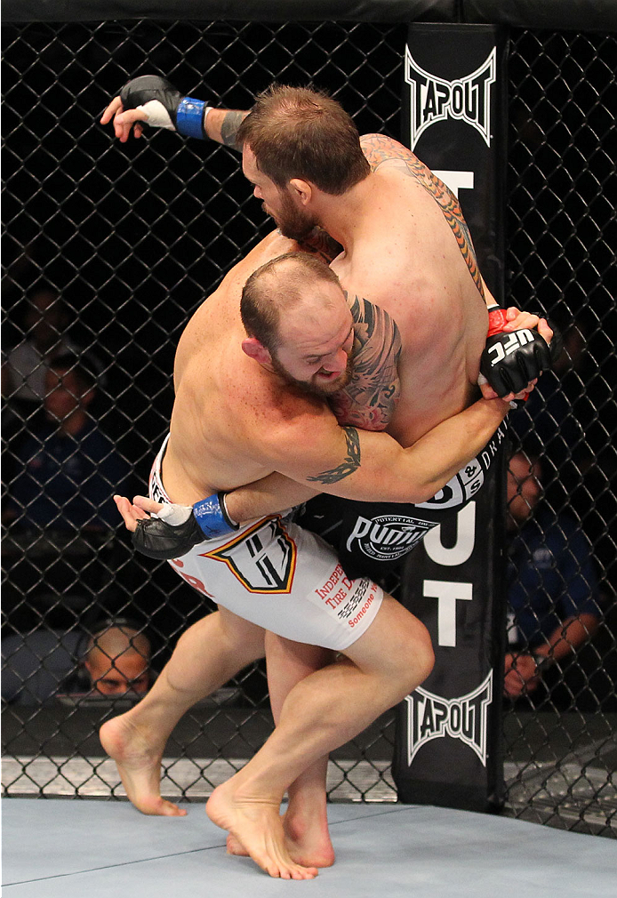 INDIANAPOLIS, IN - AUGUST 28:  (L-R) Zak Cummings takes down Benny Alloway in their welterweight fight during the UFC on FOX Sports 1 event at Bankers Life Fieldhouse on August 28, 2013 in Indianapolis, Indiana. (Photo by Ed Mulholland/Zuffa LLC/Zuffa LLC