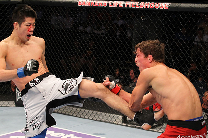 INDIANAPOLIS, IN - AUGUST 28:  (L-R) Hatsu Hioki kicks Darren Elkins in their featherweight fight during the UFC on FOX Sports 1 event at Bankers Life Fieldhouse on August 28, 2013 in Indianapolis, Indiana. (Photo by Ed Mulholland/Zuffa LLC/Zuffa LLC via