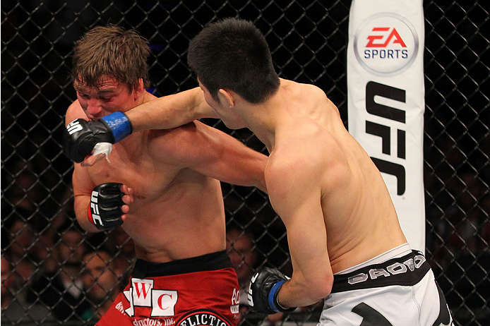 INDIANAPOLIS, IN - AUGUST 28:  (R-L) Hatsu Hioki punches Darren Elkins in their featherweight fight during the UFC on FOX Sports 1 event at Bankers Life Fieldhouse on August 28, 2013 in Indianapolis, Indiana. (Photo by Ed Mulholland/Zuffa LLC/Zuffa LLC vi