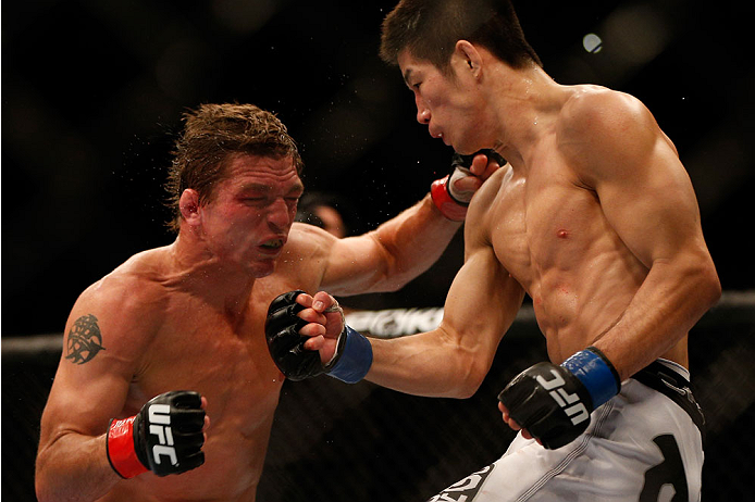 INDIANAPOLIS, IN - AUGUST 28:  (R-L) Hatsu Hioki punches Darren Elkins in their featherweight fight during the UFC on FOX Sports 1 event at Bankers Life Fieldhouse on August 28, 2013 in Indianapolis, Indiana. (Photo by Josh Hedges/Zuffa LLC/Zuffa LLC via