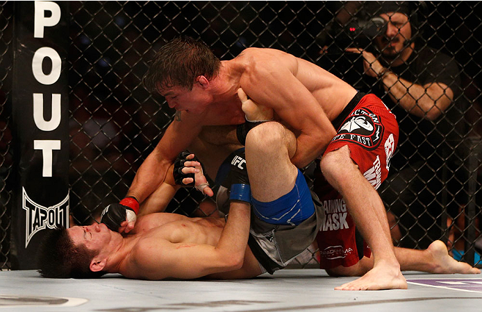 INDIANAPOLIS, IN - AUGUST 28:  (R-L) Darren Elkins punches Hatsu Hioki in their featherweight fight during the UFC on FOX Sports 1 event at Bankers Life Fieldhouse on August 28, 2013 in Indianapolis, Indiana. (Photo by Josh Hedges/Zuffa LLC/Zuffa LLC via