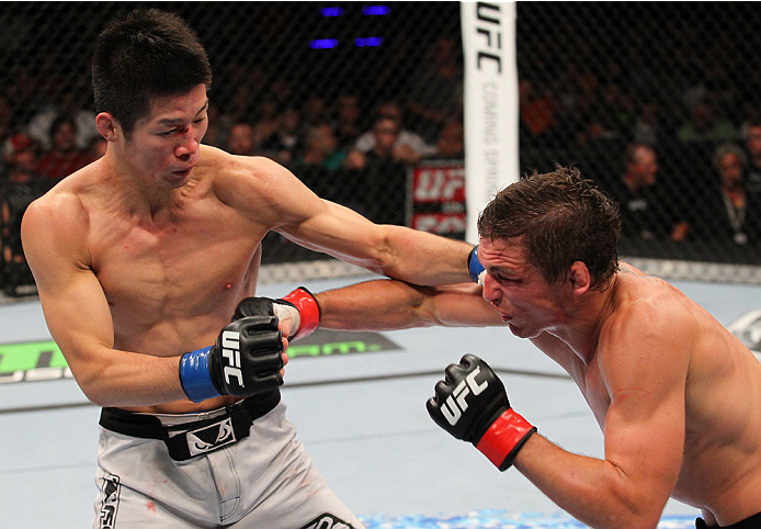 INDIANAPOLIS, IN - AUGUST 28:  (L-R) Hatsu Hioki and Darren Elkins trade punches in their featherweight fight during the UFC on FOX Sports 1 event at Bankers Life Fieldhouse on August 28, 2013 in Indianapolis, Indiana. (Photo by Ed Mulholland/Zuffa LLC/Zu