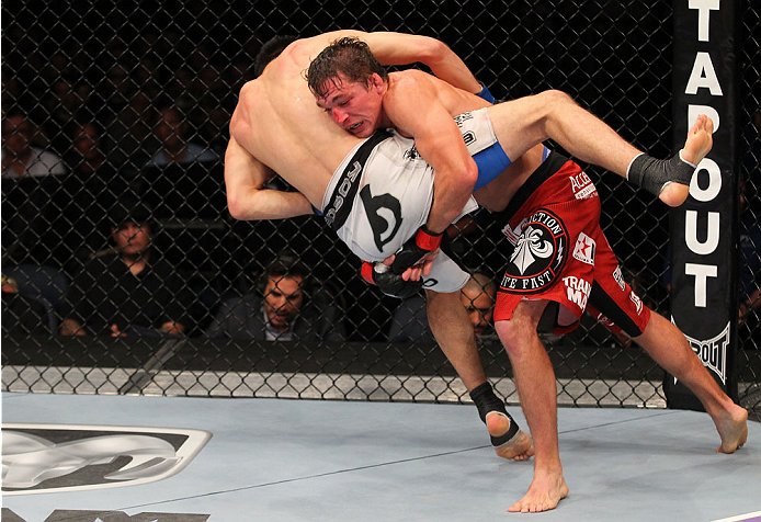 INDIANAPOLIS, IN - AUGUST 28:  (R-L) Darren Elkins takes down Hatsu Hioki in their featherweight fight during the UFC on FOX Sports 1 event at Bankers Life Fieldhouse on August 28, 2013 in Indianapolis, Indiana. (Photo by Ed Mulholland/Zuffa LLC/Zuffa LLC