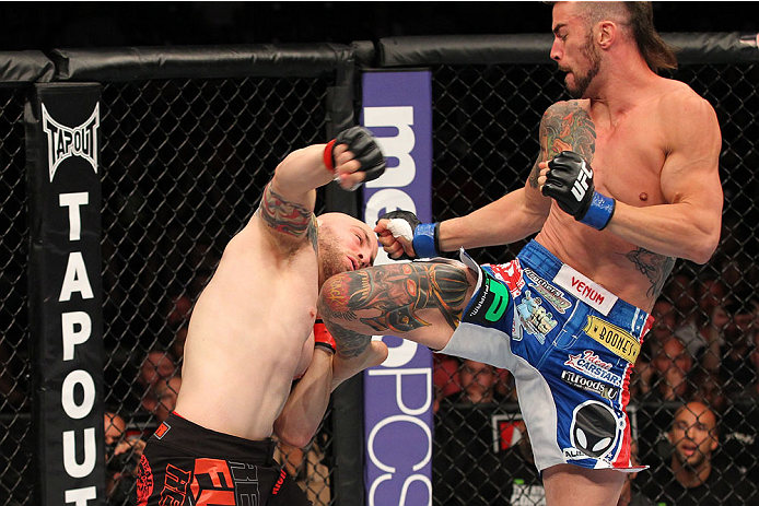 INDIANAPOLIS, IN - AUGUST 28:  (R-L) Brandon Thatch knees Justin Edwards in their welterweight fight during the UFC on FOX Sports 1 event at Bankers Life Fieldhouse on August 28, 2013 in Indianapolis, Indiana. (Photo by Ed Mulholland/Zuffa LLC/Zuffa LLC v