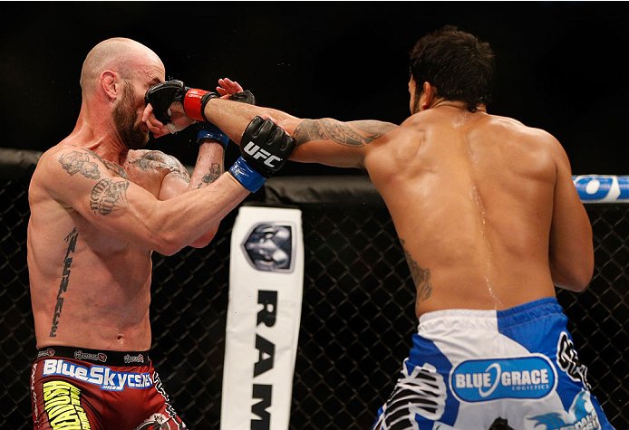 INDIANAPOLIS, IN - AUGUST 28:  (R-L) Brad Tavares punches Bubba McDaniel in their middleweight fight during the UFC on FOX Sports 1 event at Bankers Life Fieldhouse on August 28, 2013 in Indianapolis, Indiana. (Photo by Josh Hedges/Zuffa LLC/Zuffa LLC via
