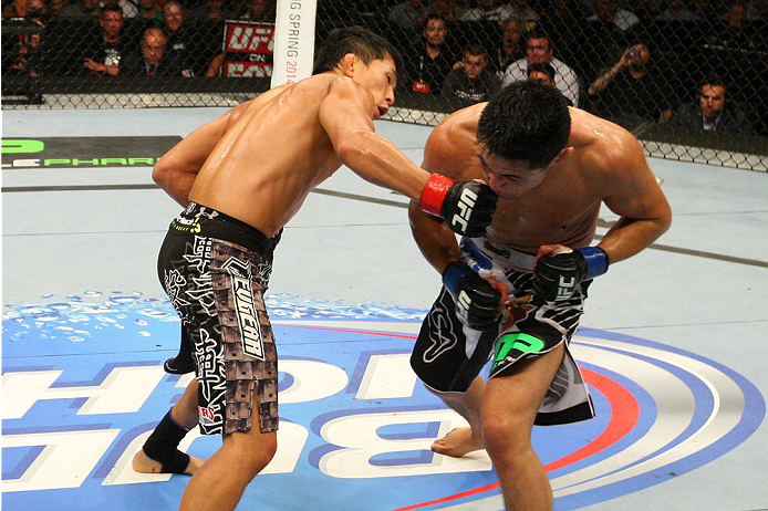 INDIANAPOLIS, IN - AUGUST 28:  (L-R) Takeya Mizugaki punches Erik Perez in their bantamweight fight during the UFC on FOX Sports 1 event at Bankers Life Fieldhouse on August 28, 2013 in Indianapolis, Indiana. (Photo by Ed Mulholland/Zuffa LLC/Zuffa LLC vi