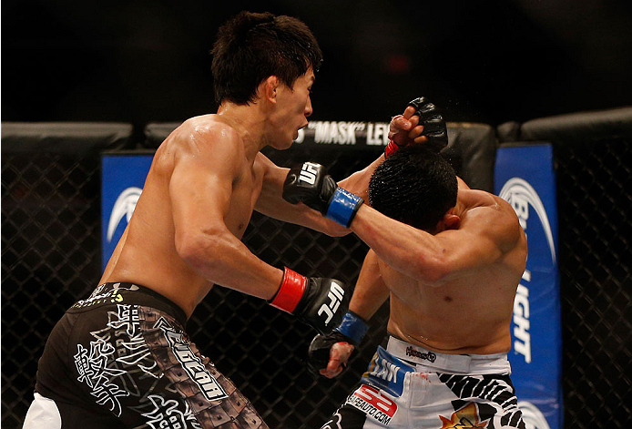 INDIANAPOLIS, IN - AUGUST 28:  (L-R) Takeya Mizugaki punches Erik Perez in their bantamweight fight during the UFC on FOX Sports 1 event at Bankers Life Fieldhouse on August 28, 2013 in Indianapolis, Indiana. (Photo by Josh Hedges/Zuffa LLC/Zuffa LLC via