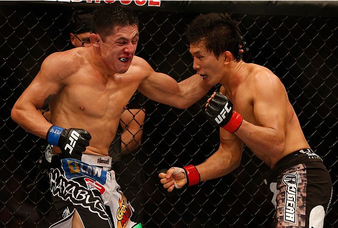 INDIANAPOLIS, IN - AUGUST 28:  (L-R) Erik Perez punches Takeya Mizugaki in their bantamweight fight during the UFC on FOX Sports 1 event at Bankers Life Fieldhouse on August 28, 2013 in Indianapolis, Indiana. (Photo by Josh Hedges/Zuffa LLC/Zuffa LLC via