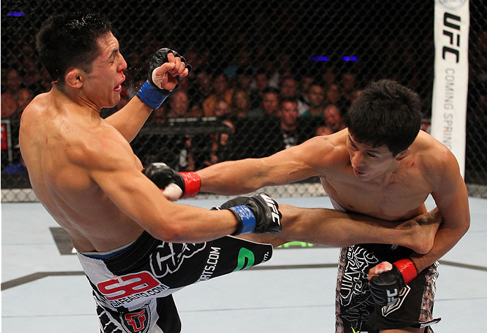 INDIANAPOLIS, IN - AUGUST 28:  (R-L) Takeya Mizugaki punches Erik Perez in their bantamweight fight during the UFC on FOX Sports 1 event at Bankers Life Fieldhouse on August 28, 2013 in Indianapolis, Indiana. (Photo by Ed Mulholland/Zuffa LLC/Zuffa LLC vi