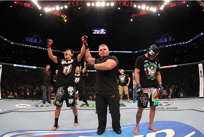 INDIANAPOLIS, IN - AUGUST 28:  Takeya Mizugaki (L) reacts after his victory over Erik Perez (R) in their bantamweight fight during the UFC on FOX Sports 1 event at Bankers Life Fieldhouse on August 28, 2013 in Indianapolis, Indiana. (Photo by Ed Mulhollan