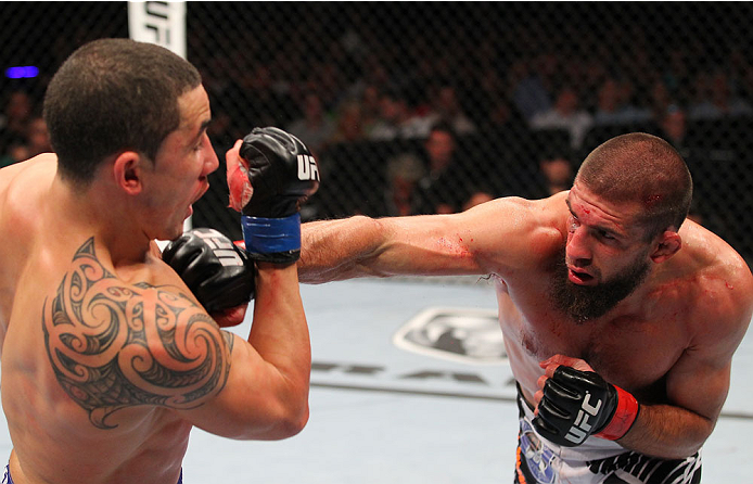INDIANAPOLIS, IN - AUGUST 28:  (R-L) Court McGee punches Robert Whittaker in their welterweight fight during the UFC on FOX Sports 1 event at Bankers Life Fieldhouse on August 28, 2013 in Indianapolis, Indiana. (Photo by Ed Mulholland/Zuffa LLC/Zuffa LLC