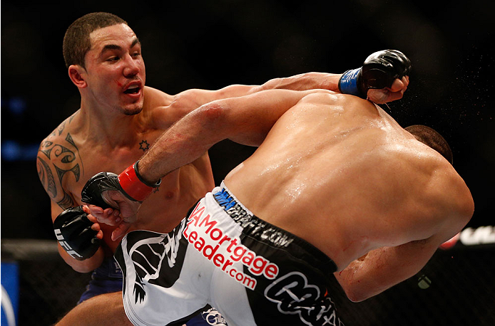 INDIANAPOLIS, IN - AUGUST 28:  (R-L) Robert Whittaker punches Court McGee in their welterweight fight during the UFC on FOX Sports 1 event at Bankers Life Fieldhouse on August 28, 2013 in Indianapolis, Indiana. (Photo by Josh Hedges/Zuffa LLC/Zuffa LLC vi