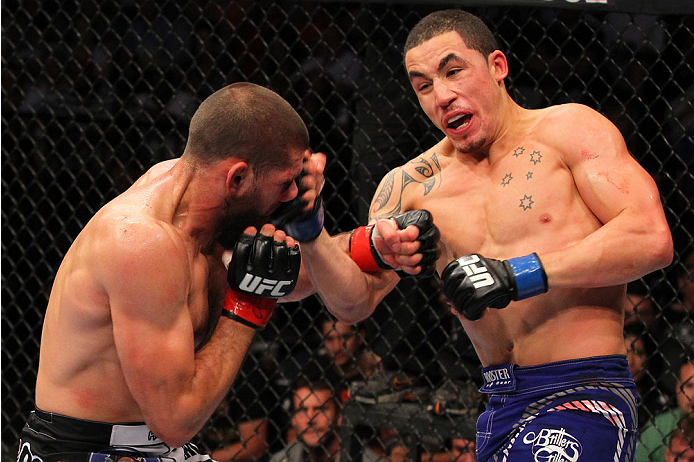 INDIANAPOLIS, IN - AUGUST 28:  (R-L) Robert Whittaker punches Court McGee in their welterweight fight during the UFC on FOX Sports 1 event at Bankers Life Fieldhouse on August 28, 2013 in Indianapolis, Indiana. (Photo by Ed Mulholland/Zuffa LLC/Zuffa LLC