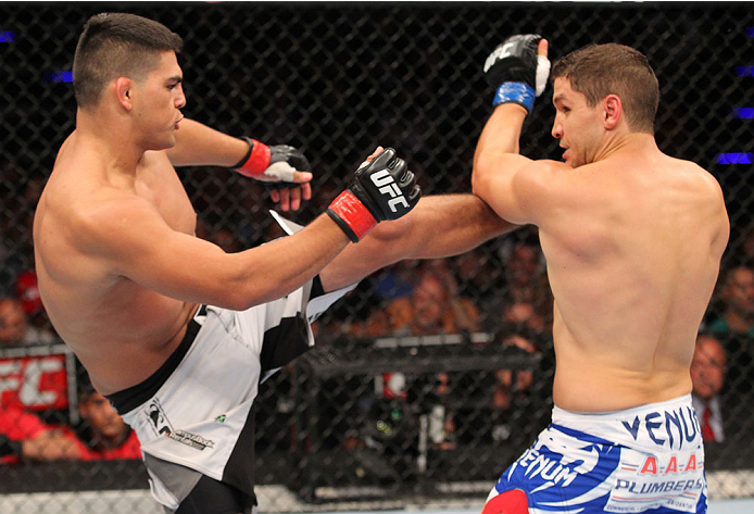 INDIANAPOLIS, IN - AUGUST 28:  (L-R) Kelvin Gastelum kicks Brian Melancon in their welterweight fight during the UFC on FOX Sports 1 event at Bankers Life Fieldhouse on August 28, 2013 in Indianapolis, Indiana. (Photo by Ed Mulholland/Zuffa LLC/Zuffa LLC