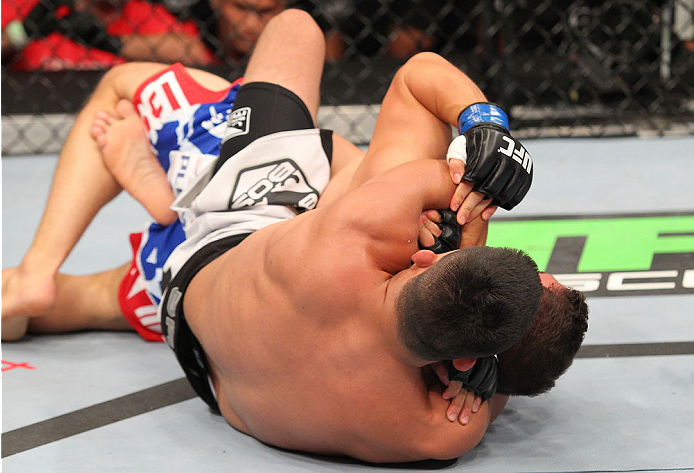 INDIANAPOLIS, IN - AUGUST 28:  (L-R) Kelvin Gastelum secures a rear choke submission against Brian Melancon in their welterweight fight during the UFC on FOX Sports 1 event at Bankers Life Fieldhouse on August 28, 2013 in Indianapolis, Indiana. (Photo by