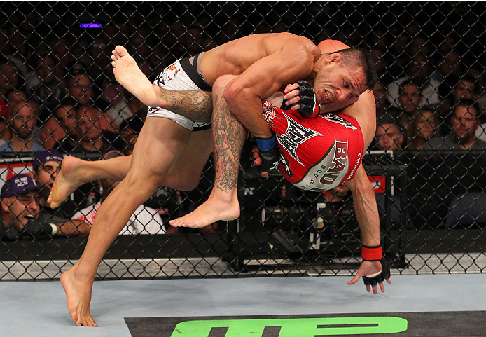 """INDIANAPOLIS, IN - AUGUST 28:  (L-R) Rafael dos Anjos takes down Donald """"Cowboy"""" Cerrone in their lightweight fight during the UFC on FOX Sports 1 event at Bankers Life Fieldhouse on August 28, 2013 in Indianapolis, Indiana. (Photo by Ed Mulholland/Zuffa"""