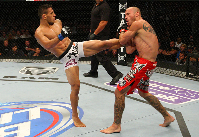 """INDIANAPOLIS, IN - AUGUST 28:  (L-R) Rafael dos Anjos kicks Donald """"Cowboy"""" Cerrone in their lightweight fight during the UFC on FOX Sports 1 event at Bankers Life Fieldhouse on August 28, 2013 in Indianapolis, Indiana. (Photo by Ed Mulholland/Zuffa LLC/Z"""