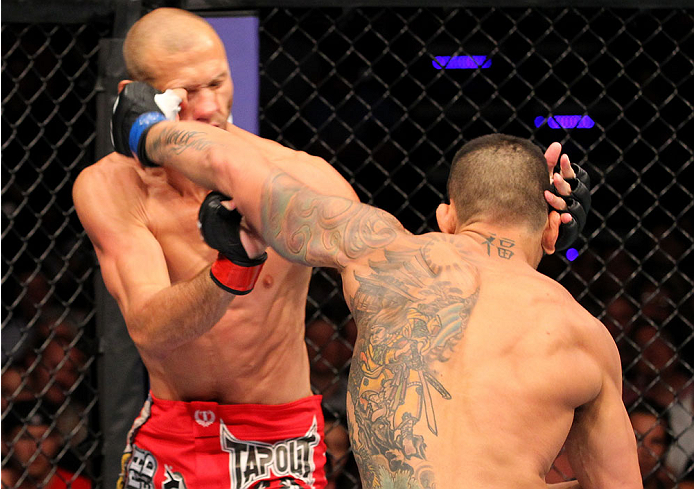 """INDIANAPOLIS, IN - AUGUST 28:  (R-L) Rafael dos Anjos punches Donald """"Cowboy"""" Cerrone in their lightweight fight during the UFC on FOX Sports 1 event at Bankers Life Fieldhouse on August 28, 2013 in Indianapolis, Indiana. (Photo by Ed Mulholland/Zuffa LLC"""