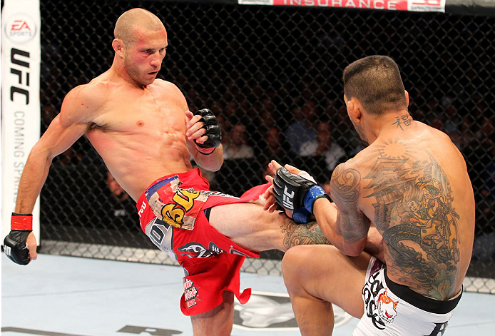 """INDIANAPOLIS, IN - AUGUST 28:  (L-R) Donald """"Cowboy"""" Cerrone kicks Rafael dos Anjos in their lightweight fight during the UFC on FOX Sports 1 event at Bankers Life Fieldhouse on August 28, 2013 in Indianapolis, Indiana. (Photo by Ed Mulholland/Zuffa LLC/Z"""