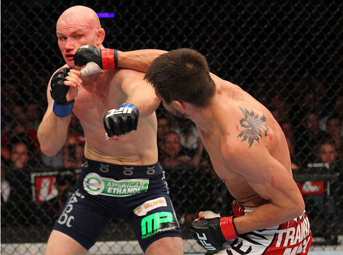 INDIANAPOLIS, IN - AUGUST 28:  (R-L) Carlos Condit punches Martin Kampmann in their welterweight fight during the UFC on FOX Sports 1 event at Bankers Life Fieldhouse on August 28, 2013 in Indianapolis, Indiana. (Photo by Ed Mulholland/Zuffa LLC/Zuffa LLC