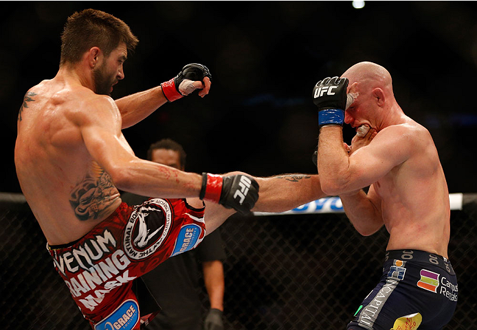 INDIANAPOLIS, IN - AUGUST 28:  (L-R) Carlos Condit kicks Martin Kampmann in their welterweight fight during the UFC on FOX Sports 1 event at Bankers Life Fieldhouse on August 28, 2013 in Indianapolis, Indiana. (Photo by Josh Hedges/Zuffa LLC/Zuffa LLC via