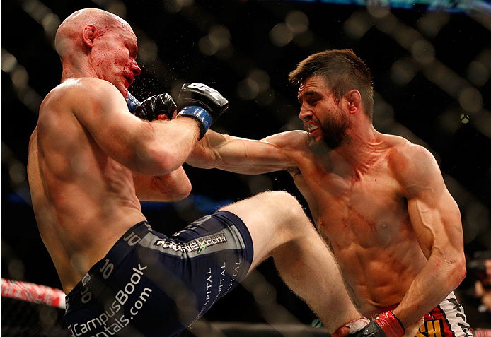 INDIANAPOLIS, IN - AUGUST 28:  (R-L) Carlos Condit punches Martin Kampmann in their welterweight fight during the UFC on FOX Sports 1 event at Bankers Life Fieldhouse on August 28, 2013 in Indianapolis, Indiana. (Photo by Josh Hedges/Zuffa LLC/Zuffa LLC v