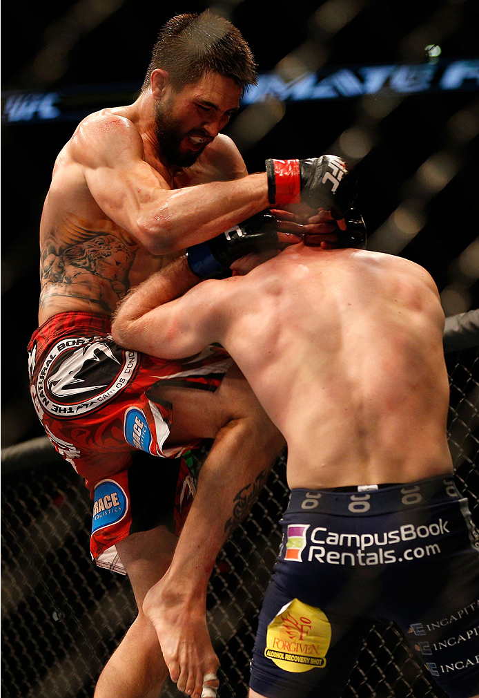 INDIANAPOLIS, IN - AUGUST 28:  (L-R) Carlos Condit knees Martin Kampmann in their welterweight fight during the UFC on FOX Sports 1 event at Bankers Life Fieldhouse on August 28, 2013 in Indianapolis, Indiana. (Photo by Josh Hedges/Zuffa LLC/Zuffa LLC via