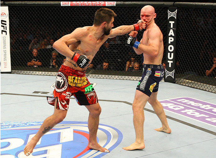 INDIANAPOLIS, IN - AUGUST 28:  (L-R) Carlos Condit punches Martin Kampmann in their welterweight fight during the UFC on FOX Sports 1 event at Bankers Life Fieldhouse on August 28, 2013 in Indianapolis, Indiana. (Photo by Ed Mulholland/Zuffa LLC/Zuffa LLC