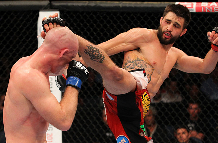 INDIANAPOLIS, IN - AUGUST 28:  (R-L) Carlos Condit kicks Martin Kampmann in their welterweight fight during the UFC on FOX Sports 1 event at Bankers Life Fieldhouse on August 28, 2013 in Indianapolis, Indiana. (Photo by Ed Mulholland/Zuffa LLC/Zuffa LLC v