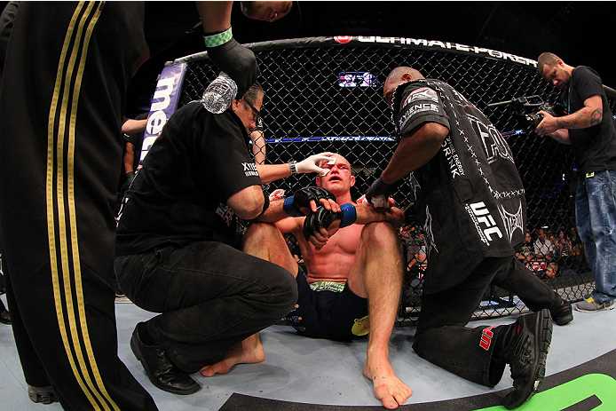 INDIANAPOLIS, IN - AUGUST 28:  Martin Kampmann is treated by cut men after his TKO loss to Carlos Condit in their welterweight fight during the UFC on FOX Sports 1 event at Bankers Life Fieldhouse on August 28, 2013 in Indianapolis, Indiana. (Photo by Ed