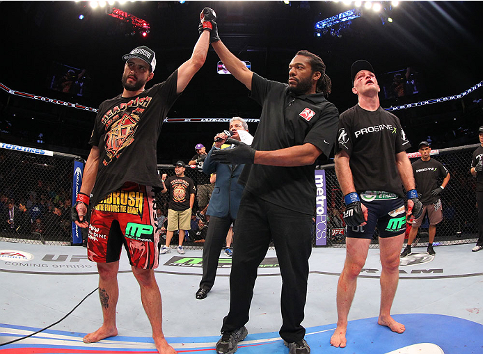 INDIANAPOLIS, IN - AUGUST 28:  Carlos Condit (L) reacts after his TKO victory over Martin Kampmann in their welterweight fight during the UFC on FOX Sports 1 event at Bankers Life Fieldhouse on August 28, 2013 in Indianapolis, Indiana. (Photo by Ed Mulhol