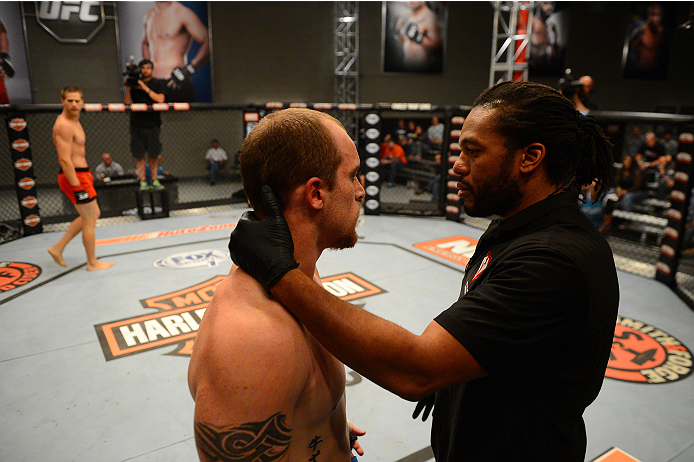 LAS VEGAS, NV - OCTOBER 16:  (R-L) Referee Herb Dean checks on Daniel Vizcaya after he was knocked down by Matt Van Buren in their elimination fight during filming of season nineteen of The Ultimate Fighter on October 16, 2013 in Las Vegas, Nevada. (Photo