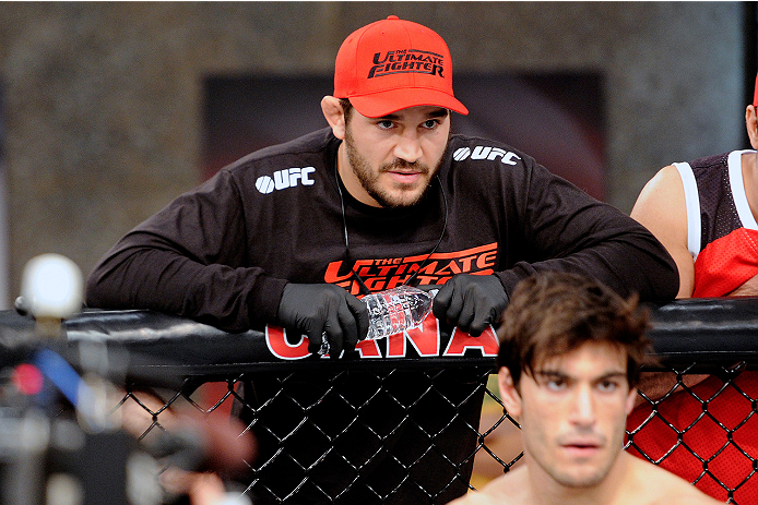 LACHUTE, CANADA - NOVEMBER 5:  Team Canada Coach Patrick Cote stands above fighter Elias Theodorou before his middleweight bout against Team Australia fighter Zein Saliba during filming of The Ultimate Fighter Nations television series on November 5, 2013