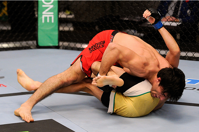 LACHUTE, CANADA - NOVEMBER 5:  Team Canada fighter Elias Theodorou (red shorts) takes down Team Australia fighter Zein Saliba in their middleweight bout during filming of The Ultimate Fighter Nations television series on November 5, 2013 in Lachute, Quebe