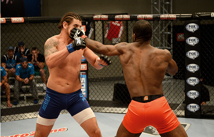 LAS VEGAS, NV - NOVEMBER 5:  (R-L) Team Edgar fighter Corey Anderson punches team Penn fighter Josh Clark in their preliminary fight during filming of season nineteen of The Ultimate Fighter on November 5, 2013 in Las Vegas, Nevada. (Photo by Al Powers/Zu