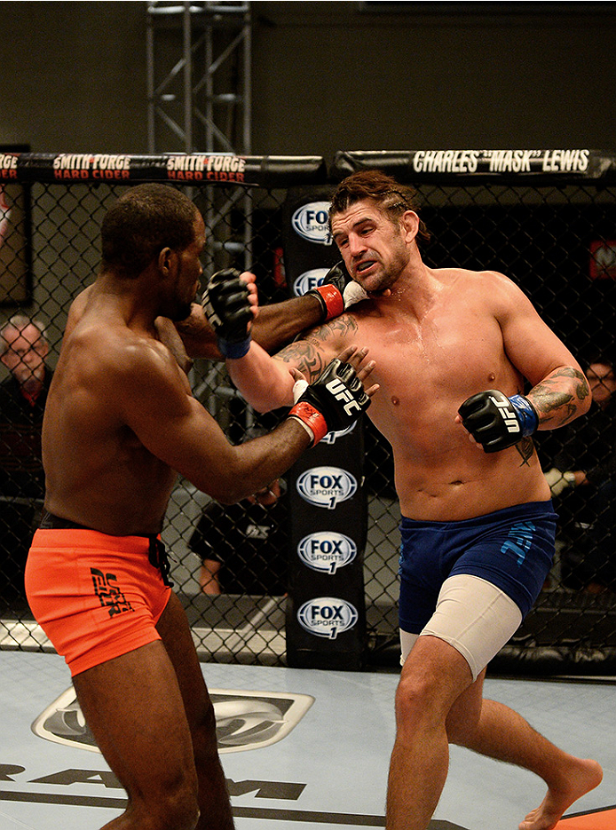 LAS VEGAS, NV - NOVEMBER 5:  (R-L) Team Penn fighter Josh Clark punches team Edgar fighter Corey Anderson in their preliminary fight during filming of season nineteen of The Ultimate Fighter on November 5, 2013 in Las Vegas, Nevada. (Photo by Al Powers/Zu