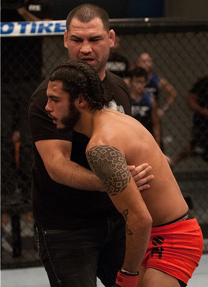 LAS VEGAS, NV - JUNE 10:  Team Velasquez fighter Marco Beltran is helped up by Head Coach Cain Valasquez after facing team Werdum fighter Guido Cannetti in their preliminary fight during filming of The Ultimate Fighter Latin America on June 10, 2014 in La