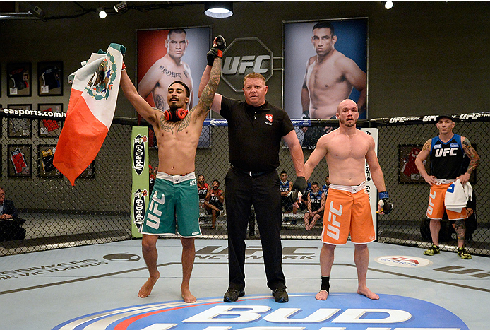 LAS VEGAS, NV - MAY 19:  (L-R) Team Velasquez fighter Jose Quionez celebrates his victory over team Werdum fighter Bentley Syler in their preliminary fight during filming of The Ultimate Fighter Latin America on May 19, 2014 in Las Vegas, Nevada. (Photo b