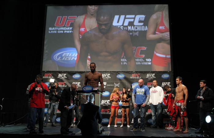 """TORONTO, ON - DECEMBER 09:  UFC Light Heavyweight Champion Jon """"Bones"""" Jones weighs in as opponent Lyoto Machida (red shorts) looks on during the UFC 140 Official Weigh-in at the Air Canada Centre on December 9, 2011 in Toronto, Canada.  (Photo by Josh He"""