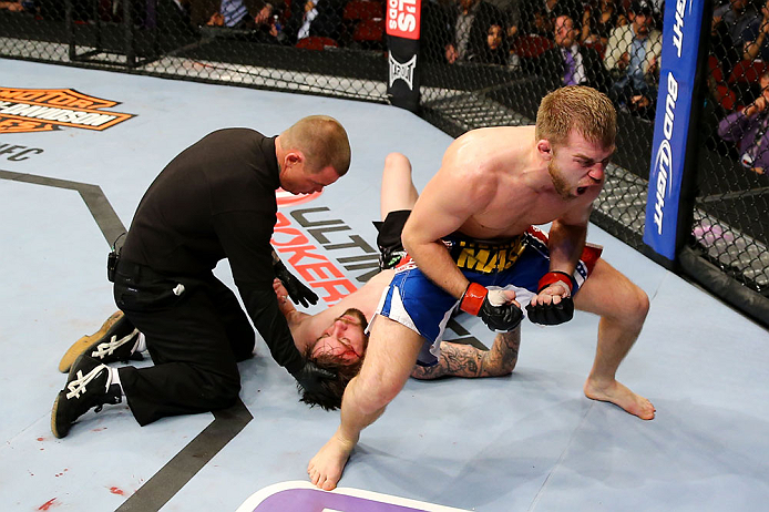 NEWARK, NJ - APRIL 27:  Bryan Caraway (R) celebrates winning by submission (guillotine choke) against Johnny Bedford (C) in their bantamweight bout during the UFC 159 event at the Prudential Center on April 27, 2013 in Newark, New Jersey.  (Photo by Al Be