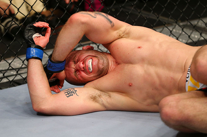 NEWARK, NJ - APRIL 27:  Alan Belcher reacts after being poked in the eye in the third round of his middleweight bout against Michael Bisping of England during the UFC 159 event at the Prudential Center on April 27, 2013 in Newark, New Jersey.  (Photo by A