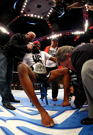 NEWARK, NJ - APRIL 27:  Jon Jones (C) has his broken toe tended to while he is interviewed by Joe Rogan (R) after winning by knockout in round one against Chael Sonnen in their light heavyweight championship bout during the UFC 159 event at the Prudential