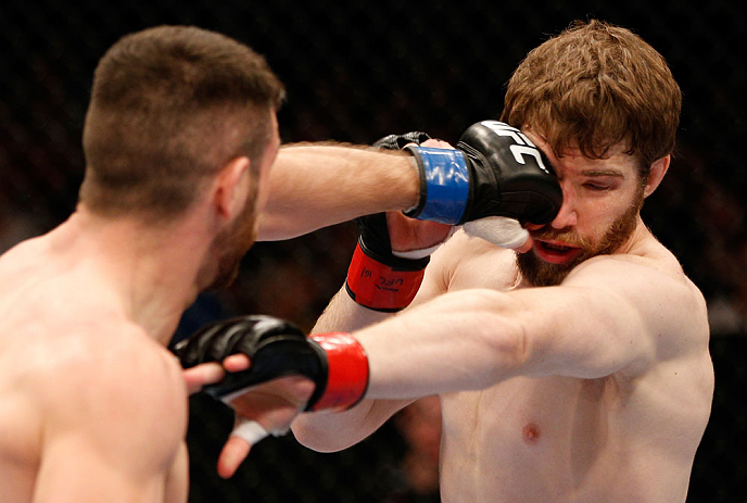 WINNIPEG, CANADA - JUNE 15:  (L-R) John Maguire punches Mitch Clarke in their lightweight fight during the UFC 161 event at the MTS Centre on June 15, 2013 in Winnipeg, Manitoba, Canada.  (Photo by Josh Hedges/Zuffa LLC/Zuffa LLC via Getty Images)