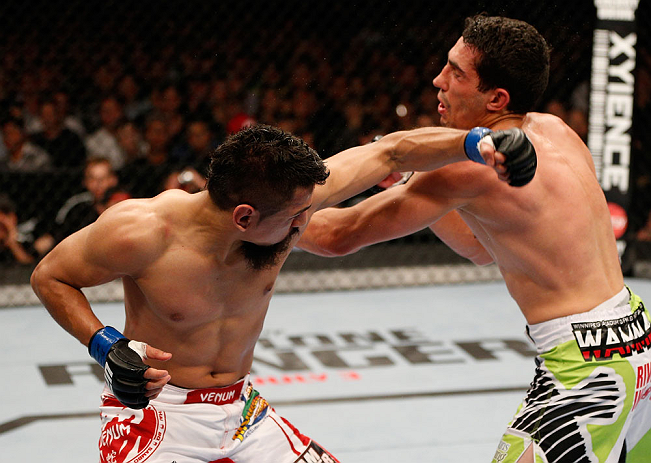 WINNIPEG, CANADA - JUNE 15:  (L-R) Edwin Figueroa punches Roland Delorme in their bantamweight fight during the UFC 161 event at the MTS Centre on June 15, 2013 in Winnipeg, Manitoba, Canada.  (Photo by Josh Hedges/Zuffa LLC/Zuffa LLC via Getty Images)