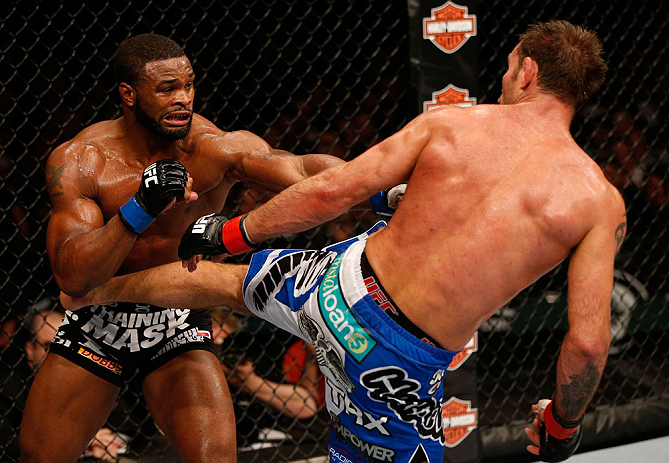 WINNIPEG, CANADA - JUNE 15:  (R-L) Jake Shields kicks Tyron Woodley in their welterweight fight during the UFC 161 event at the MTS Centre on June 15, 2013 in Winnipeg, Manitoba, Canada.  (Photo by Josh Hedges/Zuffa LLC/Zuffa LLC via Getty Images)
