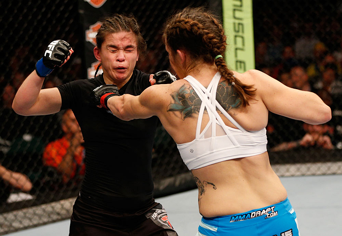 WINNIPEG, CANADA - JUNE 15:  (R-L) Alexis Davis punches Rosi Sexton in their bantamweight fight during the UFC 161 event at the MTS Centre on June 15, 2013 in Winnipeg, Manitoba, Canada.  (Photo by Josh Hedges/Zuffa LLC/Zuffa LLC via Getty Images)
