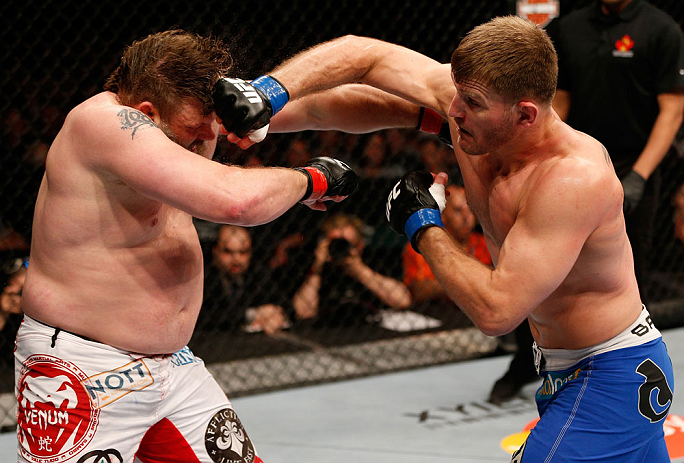 """WINNIPEG, CANADA - JUNE 15:  (R-L) Stipe Miocic punches """"Big Country"""" Roy Nelson in their heavyweight fight during the UFC 161 event at the MTS Centre on June 15, 2013 in Winnipeg, Manitoba, Canada.  (Photo by Josh Hedges/Zuffa LLC/Zuffa LLC via Getty Ima"""