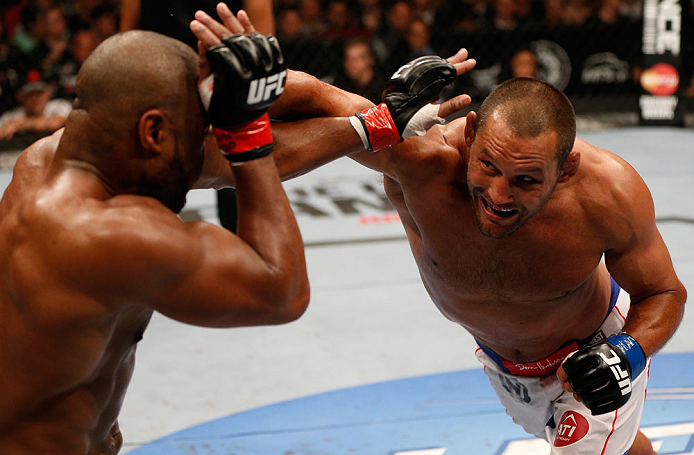 WINNIPEG, CANADA - JUNE 15:  (R-L) Dan Henderson punches Rashad Evans in their light heavyweight fight during the UFC 161 event at the MTS Centre on June 15, 2013 in Winnipeg, Manitoba, Canada.  (Photo by Josh Hedges/Zuffa LLC/Zuffa LLC via Getty Images)